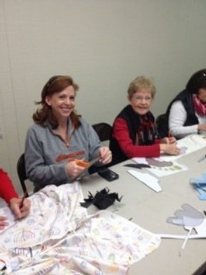 Women work on cutting out shoe patterns at a Sole Hope shoe cutting party at Concord Baptist Church.